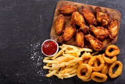 fast food products : onion rings, french fries and fried chicken on dark table, top view