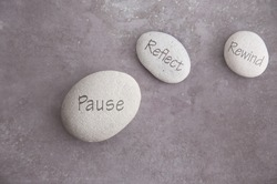 Fast forward and rewind symbols on either side of zen stone, pause reflect and rewind