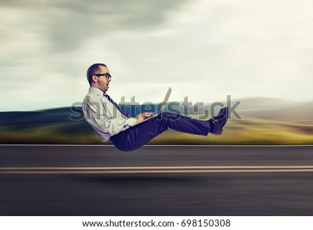 Fast internet concept. Levitating business man on road using laptop computer  #698150308
