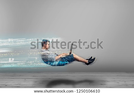Fast levitating man in a white room using a laptop. High speed browsing. #1250106610