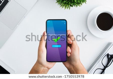 Fast Money Transfers. Woman Holding Smartphone With Transaction Completed Message On Screen, Sitting At Desk In Office, Top View Foto stock ©