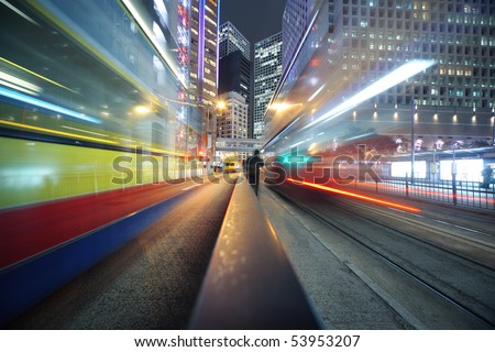 Fast moving bus lights blurred over modern city background #53953207