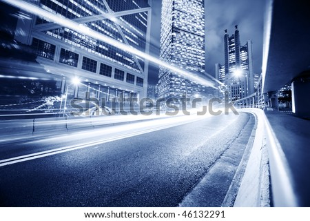 Fast moving cars lights blurred over modern city background