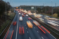 Fast moving traffic drives along the M42 in Warwickshire during evening rush hour, leaving traffic light trails as the vehicles are controlled using Active Traffic Management for each motorway lane