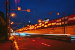 Fast night driving traffic of city, tunnel entrance. Abstract blurred background of urban moving cars. Transportation