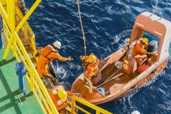 Fast rescue craft or dinghy used during emergency drill for construction barge at oil field