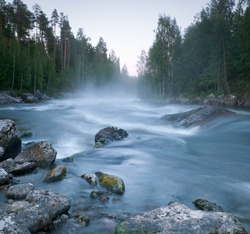 fast river in northern Russia is covered in mist