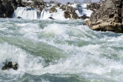 Fast river water with rocks, foam and splashes. Great Falls river bank. Virginia. USA