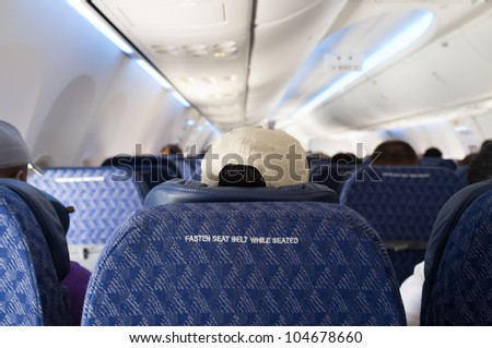 Fasten seat belt sign on the back of a seat from a commercial airliner.