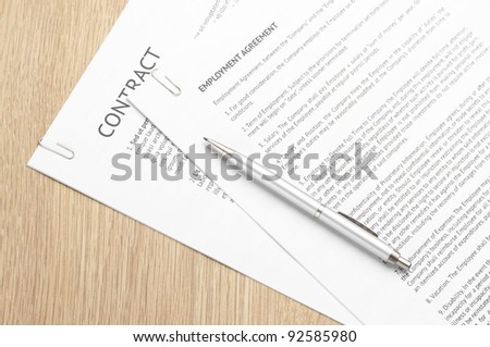 Fastened pages with legal documents and pen on wooden desk.