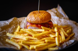 Fastfood delivery.Hamburger&french fries prepared for dinner in American fast food cafe,delivered for dinner meal in brown paper.Delicious cheeseburger&potato chips cooked in diner cafe