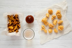 Fastfood: fried potato wedges in paper box, chicken bites, barbecue sauce and beer on a white wooden background, top view. Flat, overhead.