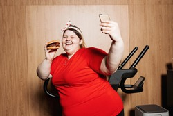 Fat and funny girl dressed in the sportswear and with a bandage on her head is making selfie standing with burger in her hand next to the treadmill