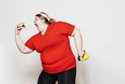 Fat and funny girl dressed in the sportswear and with a bandage on her head is standing with a burger in the one hand and the weight in the other against a white wall