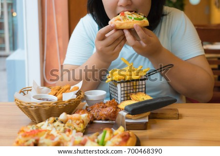 Fat asian woman bite pizza and have big meal in fast food restaurant,unhealthy girl is overweight