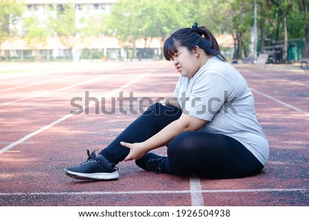 Fat Asian woman injured from jogging Sitting on the floor, holding the right ankle, felt a lot of pain. Concepts of weight loss, exercise, health problems Сток-фото ©