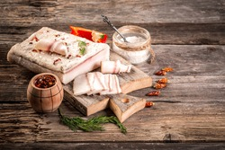 fat bacon on a wooden board. Close-up fat bacon with garlic and spices, homemade lard, top view banner menu recipe place for text.