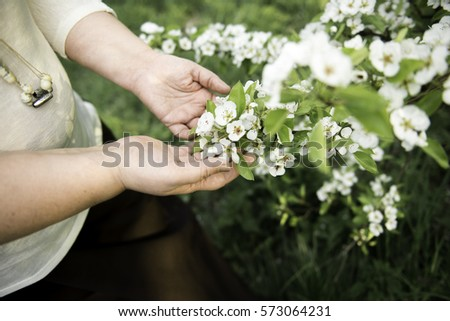 fat beautiful woman holding flowering tree branch in hands #573064231
