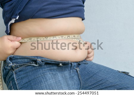 Fat boy measuring his belly with measurement tape