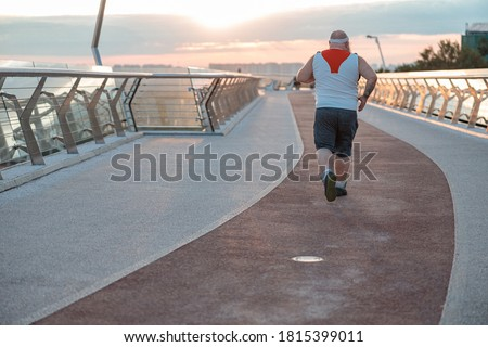 Fat caucasian bearded and bold man is doing morning exercses to loose his weight Сток-фото ©