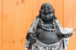Fat laughing Buddha, wooden background, god hotei.