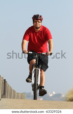 Fat man cycling on the countryside making exercise