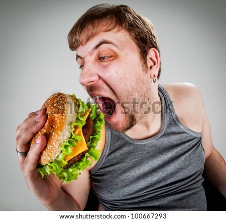 fat man eating hamburger seated on armchair