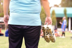 Fat man holding football boots and stands watching soccer practice.