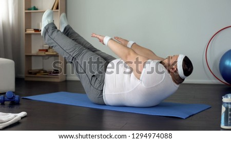 Fat man practicing abdominal static exercise, strength and endurance development
