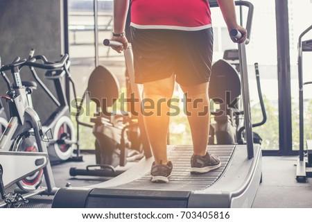 fat man walking on treadmill at fitness gym