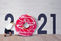 Fat man wearing sportswear while pushing a big donuts with number 2021 background in the studio