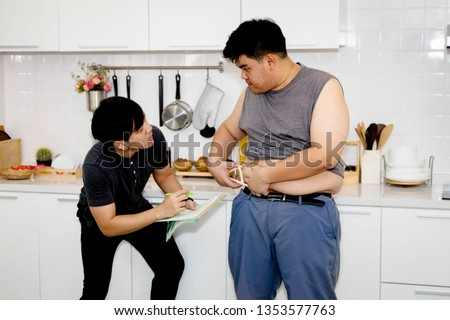 Fat man, 20 years old, use Fat Caliper Manual to measure plastic waist circumference to see the amount of fat in our body, with nutrition and dietary control experts taking note of close care.