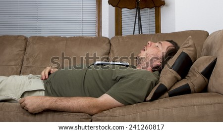 Fat obese man fell asleep on the couch with a remote on his chest