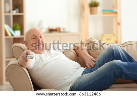 Fat senior man watching TV while lying on sofa at home. Sedentary lifestyle concept #663112486