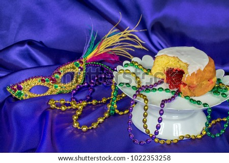 Fat Tuesday paczki with Mardi Gras party beads on white pedestal plate with sequin mask on purple satin #1022353258
