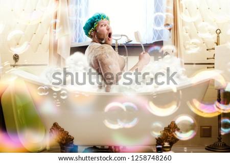 Fat ugly man washing in a bath