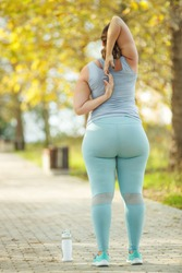 Fat woman and sports. Does exercise for weight loss in the fresh air. High quality photo.