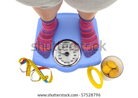 Fat woman body part in a scale and a jar of cookies