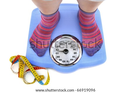 Fat woman body part in a scale and a measuring tape