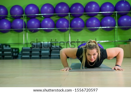 Fat woman doing aerobics in the fitness room. A girl with a lot of overweight trying to lose weight with the help of sports and yoga, does push-ups.