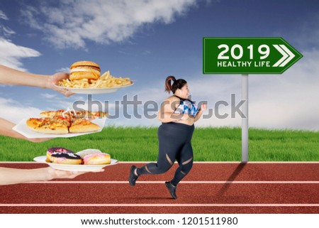 Fat woman escapes from unhealthy foods offered while running on the track with text of 2019 healthy life on the green signpost #1201511980
