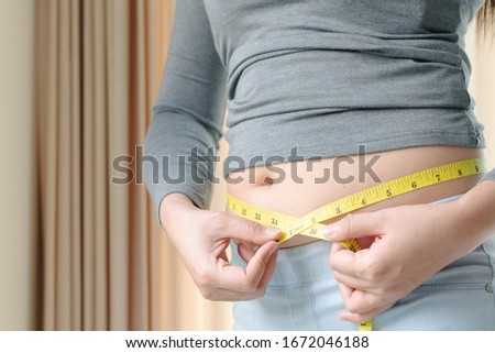 Fat woman hand holding measurement tape on her belly fat. woman diet lifestyle and build muscle concept. Сток-фото ©