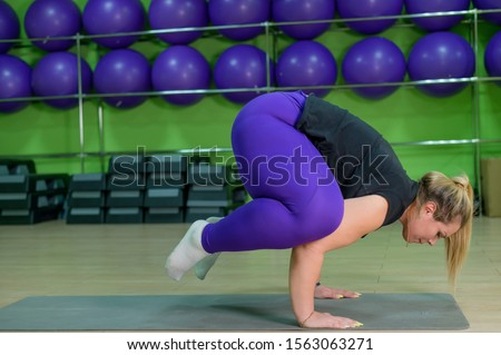 Fat woman is engaged in pilates in a fitness gym. A girl with a lot of overweight trying to lose weight with the help of yoga, stands in a raven pose. The blonde performs a bokasana.