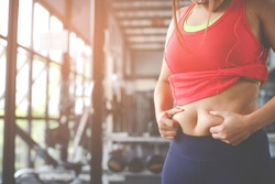 Fat woman, Obese woman hand holding excessive belly fat isolated on gym background, Overweight fatty belly of woman, Woman diet lifestyle concept to reduce belly and shape up healthy stomach muscle.