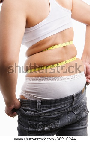 Fat woman trying to wear tight jeans from backside with measuring tape around her belly - stock photo