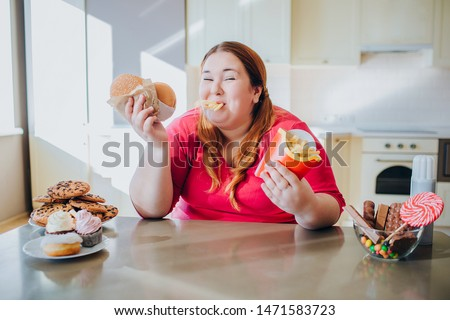 Fat young woman in kitchen sitting and eating junk food. French fries in mouth. Looking on camera and smile. Body positive. Burgers in hands. Unhealthy lifestyle. #1471583723