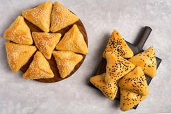 Fatayer samosa with white cheese and black sesame seeds on wooden board.