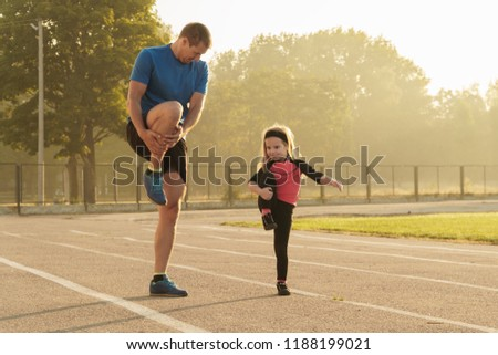 Fathe and daughter go in sports.Child at the stadium.Jogging family.Man and girl.Family spending time together.Child education.