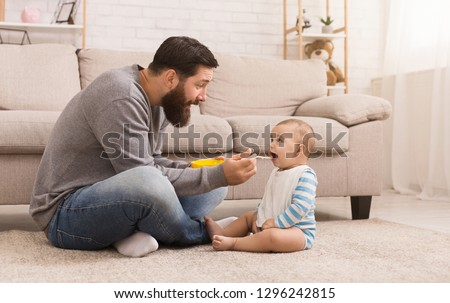 Father acting Mom feeding his baby son, sitting on floor at home, copy space
