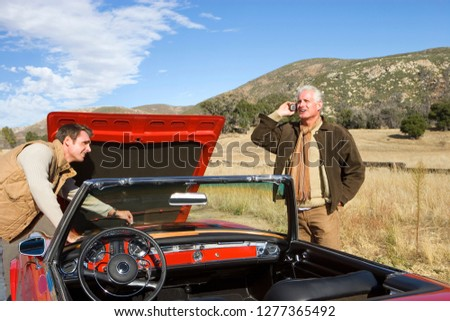 Father and adult son breakdown with classic car using mobile phone
